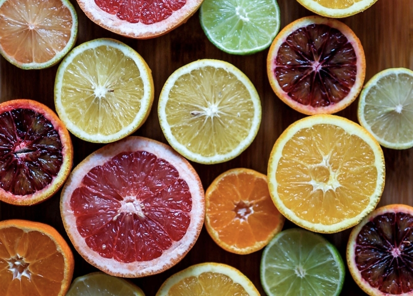 Picture of different color citric fruits, sliced in half.
