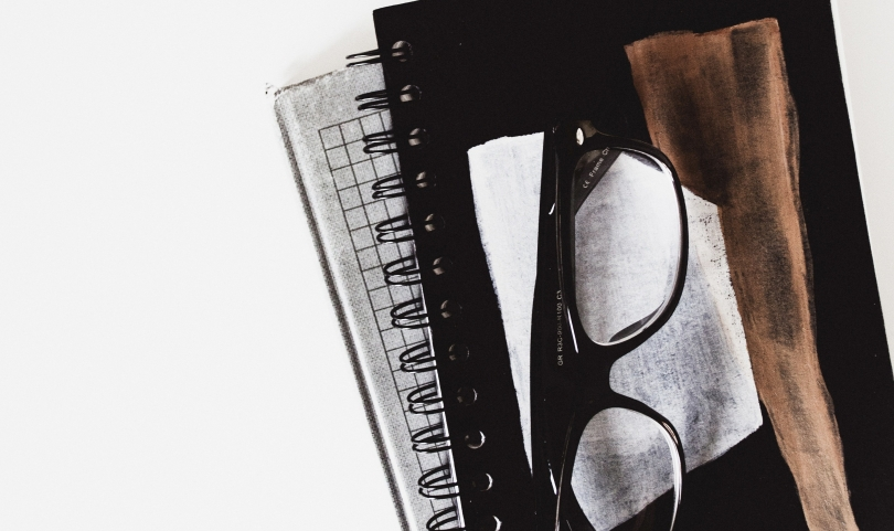 Notebook with glasses on top
