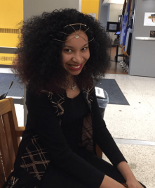 Jada Martin smiles on a bench in Vandenberg Hall, Oakland University.