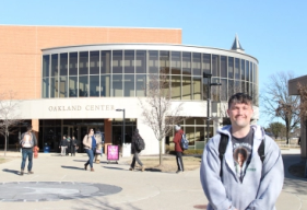 Jones smiles in front of the Oakland Center on OU's campus