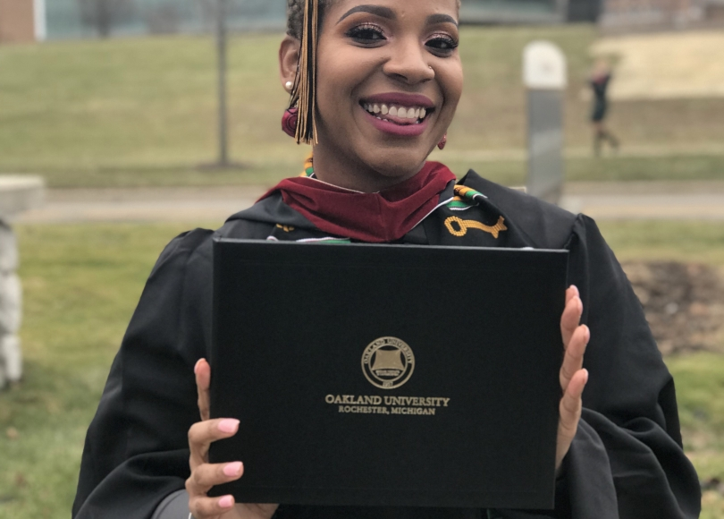 Young African American woman in cap and gown, holding Oakland University diploma, smiles.