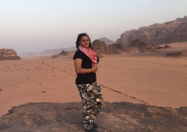 Young woman, in camouflage-style pants, black shirt, and red-and-white scarf, smiles in the desert, in Jordan.