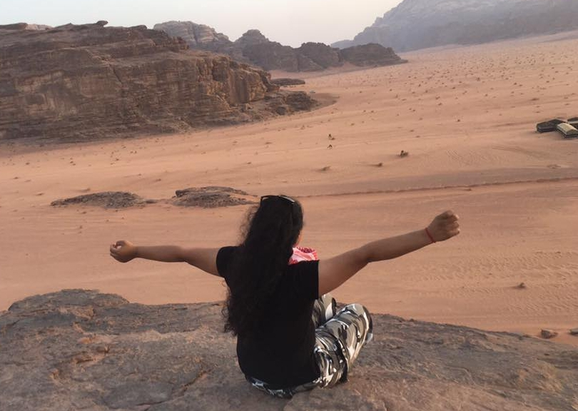 Woman sits on rock above desert line, cliffs in the background; she faces away, arms stretched wide.