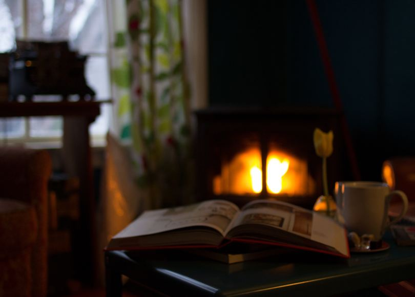 Open book near white mug, fireplace lit in background