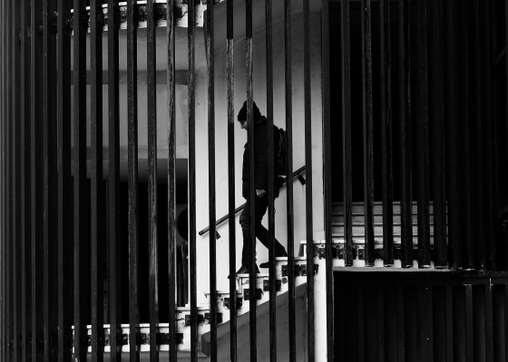Black-and-white image of man with hat and backpack going down stairs, behind decorative bars.
