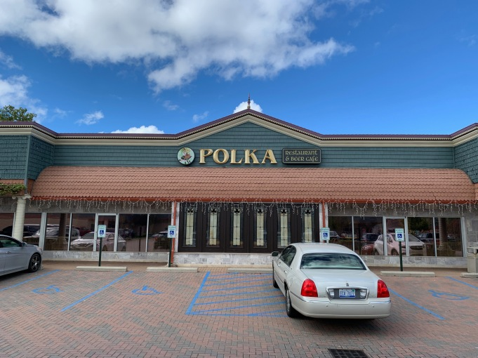Front of Polka restaurant, some of the parking lot visible in front of it, a car parked in the center.