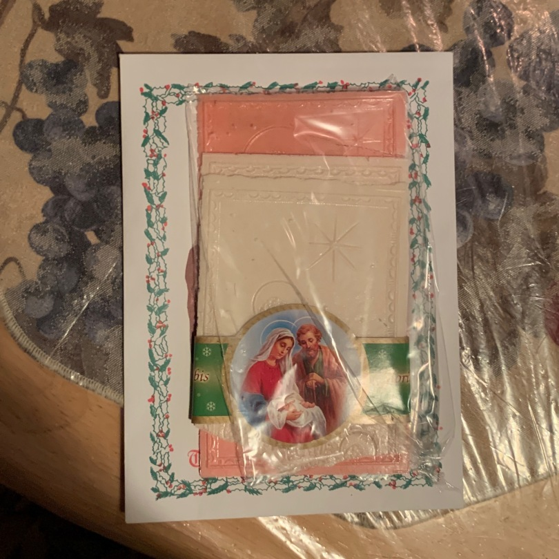 Light yellow and pink wafers in plastic cover, along with a Christian religious picture.