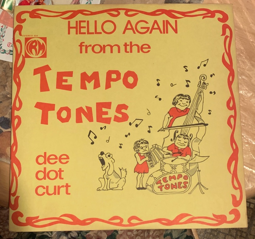 """Close-up of record cover, yellow with red font that reads """"Hello again from the Tempo Tones. Dee dot curt. Tempo Jones."""""""