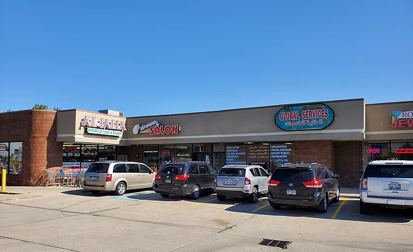Store fronts in strip mall, many have text in Arabic in signs.