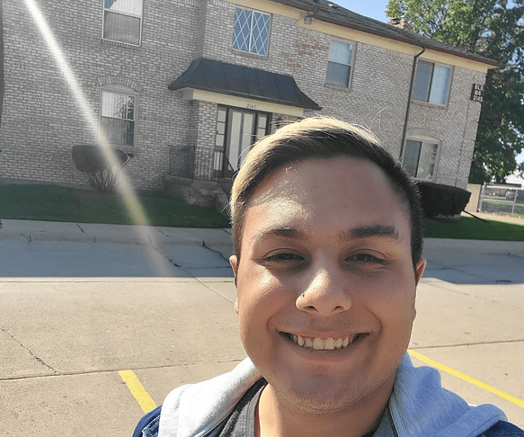 Selfie of smiling young man, in front of apartment building.