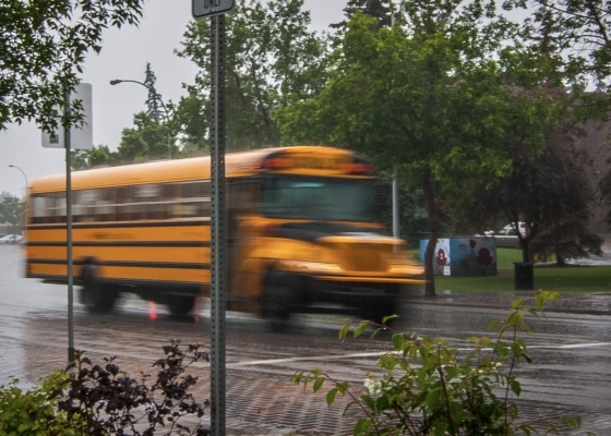 Yellow school bus on road during rain