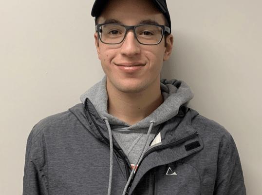 Young man with Oakland University baseball cap smiles.