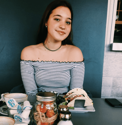 Young woman smiles, sitting at table, food in front of her.