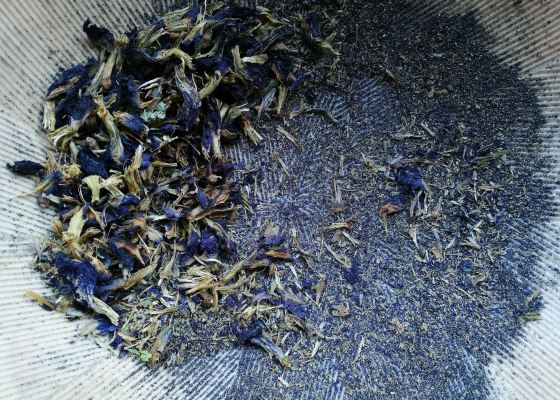 Dried blue flowers, partly grounded into a powder in a mortar.