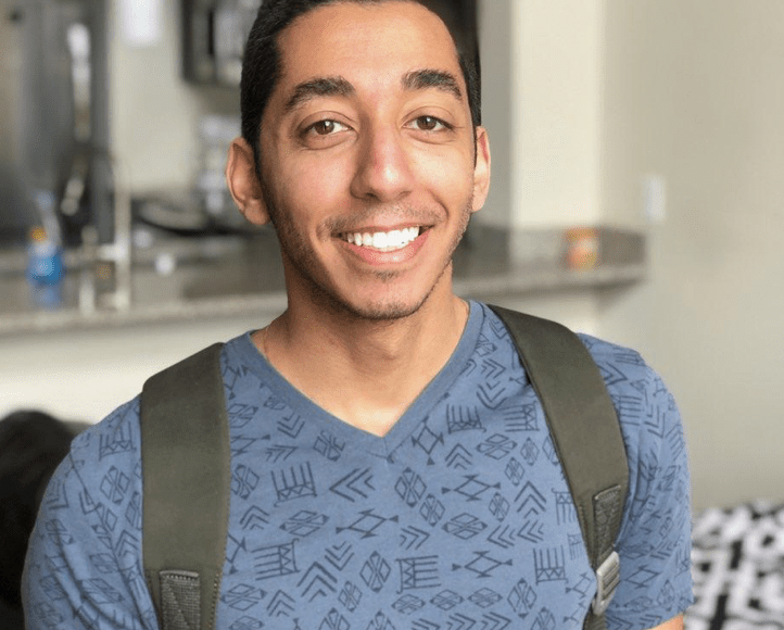 Young man smiles at camera, kitchen in background