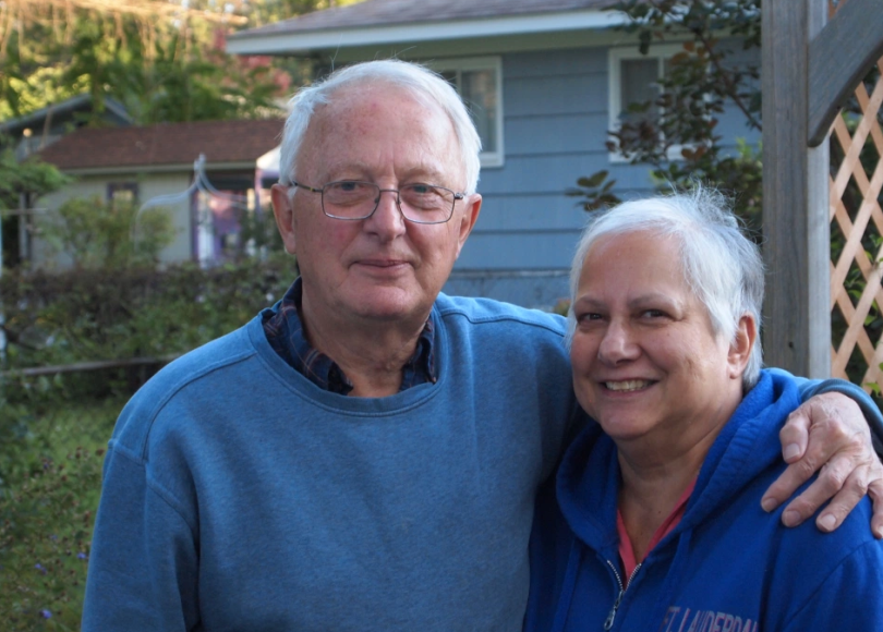 An elderly couple smile, his arm around her shoulders, view of a backyard and blue house behind them.