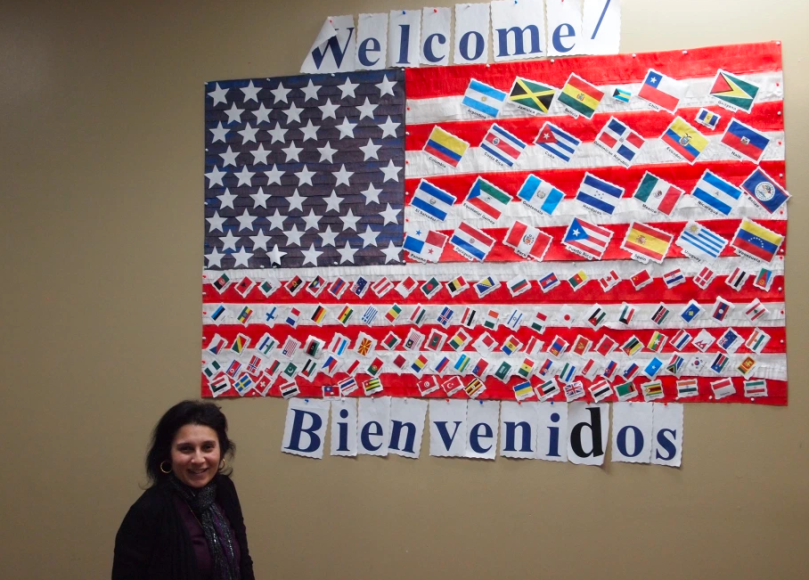 "Woman smiles by U.S. flag on the wall, which is covered in smaller flags from many countries. The sign ""welcome"" sits above the flag and ""Bienvenidos"" (""Welcome"" in Spanish) below it."