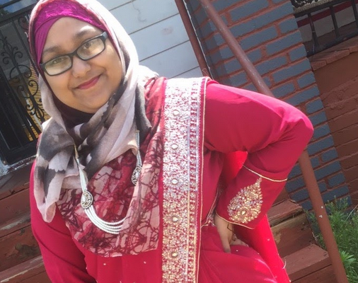 Young woman wearing glasses smiles to camera, as she poses with a red sari and grey and pink head scarf.