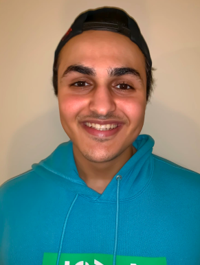 Close-up of young man smiling, wears blue hoodie and backwards baseball cap.