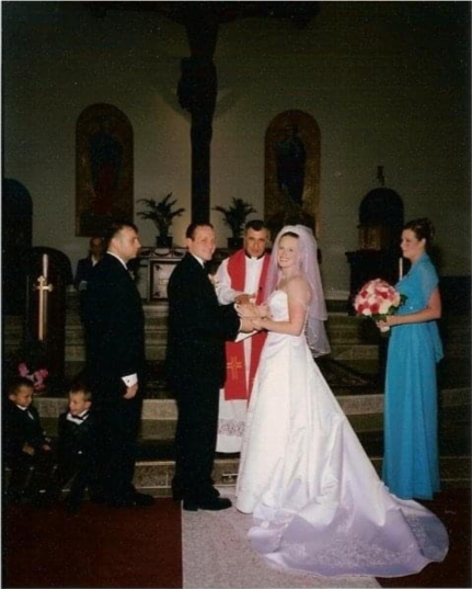 Wedding setting, bride and group, framed by maid of honor on one side and groomsmen and two small children on the other side, officiating priest in the background, church setting