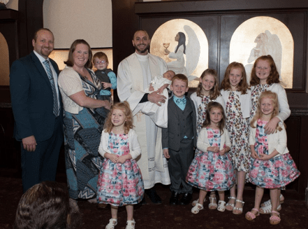 Family poses for picture, parents holding small child on left, six girls in matching outfits, two boys in matching outfits, priest in the center holding baby dressed in white, Catholic church setting