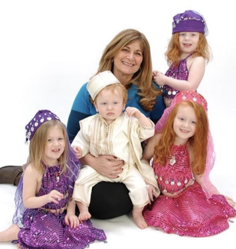 Woman smiles posing with four small children, outfits in Middle Eastern style