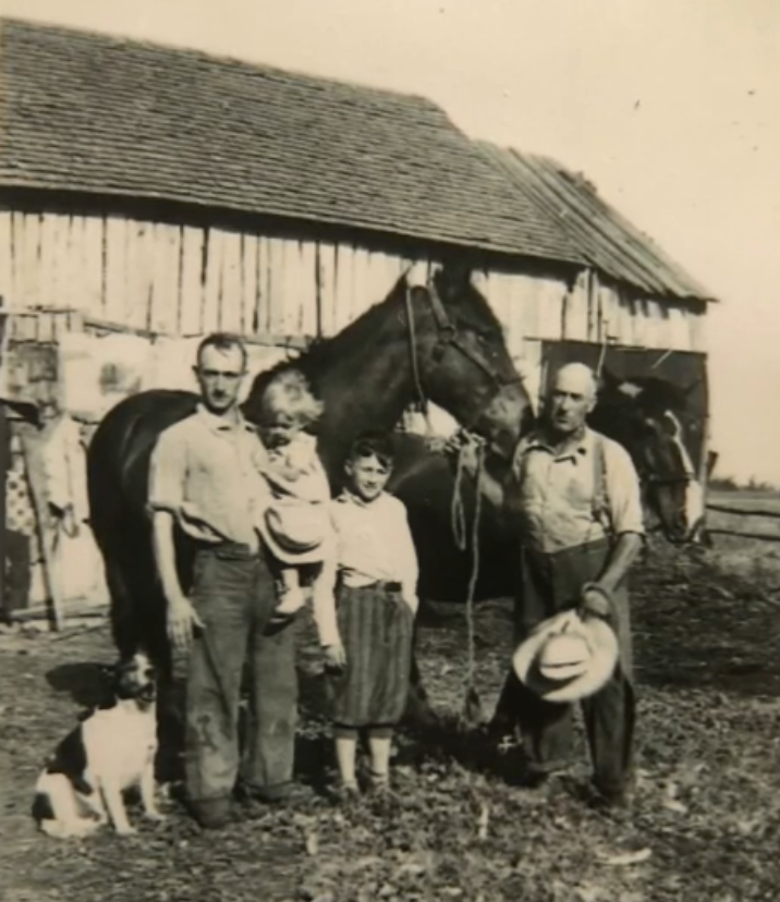 Black-and-white photo of two men, two children, a dog, and two horses in front of a barn.