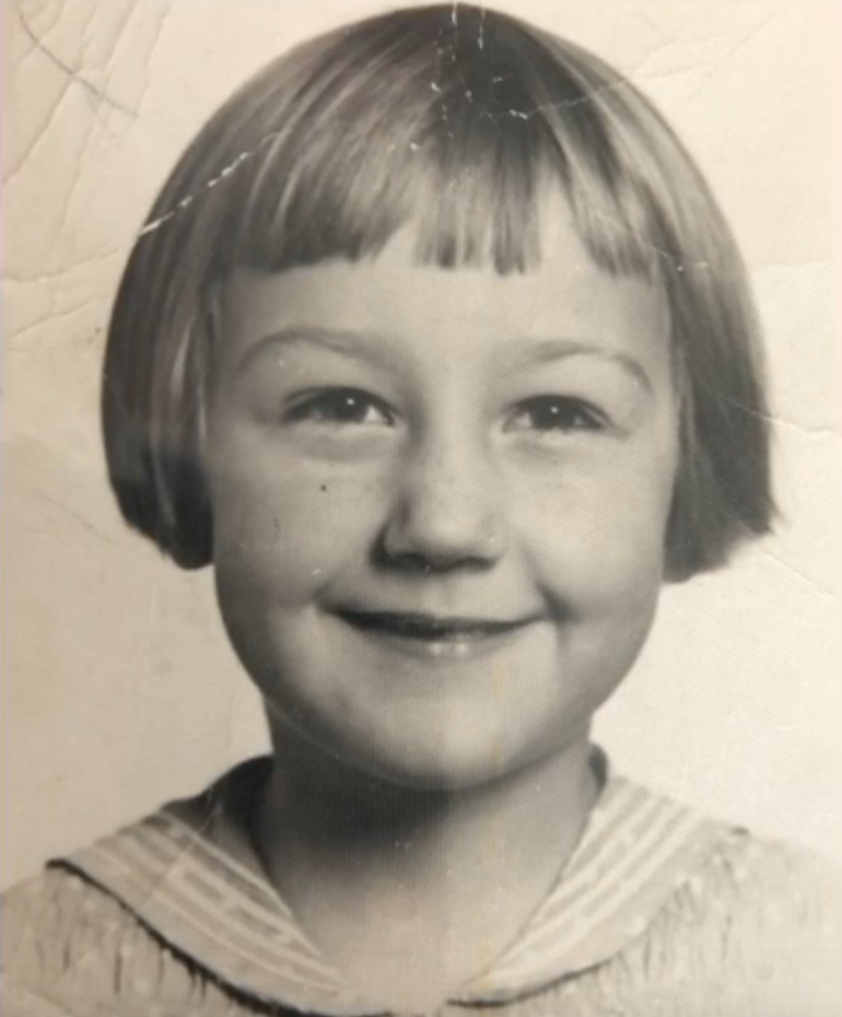 Close-up of white little girl smiling, bowl haircut, black-and-white photo