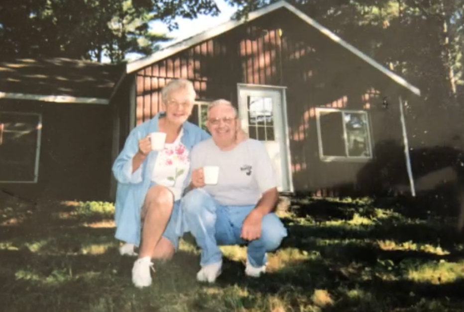 Older couple by red and white house and trees, squating down holding white coffee mugs, smiling, both with white hair
