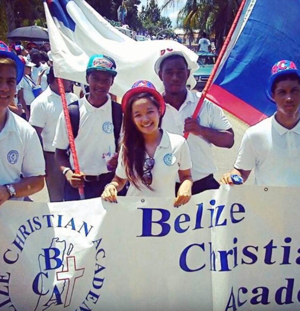 "Four teenagers holding a white and blue banner sign that reads ""Belize Christian Academy"" and has cross and symbol on it. Center is a young woman of Asian heritage."