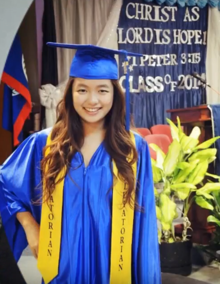 Young woman of Asian heritage smiles in graduation outfit