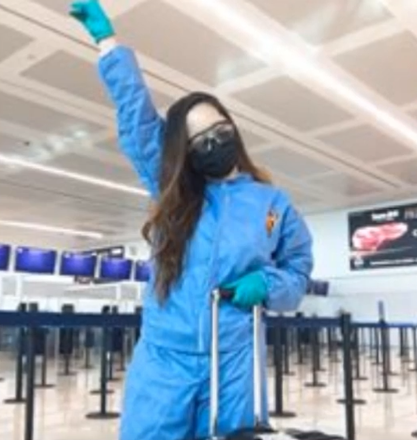 Woman with long hair in blue outfit, wearing plastic glasses, black face mask, and blue gloves, holds suitcase with empty airport setting in the background, pumping her fist up.