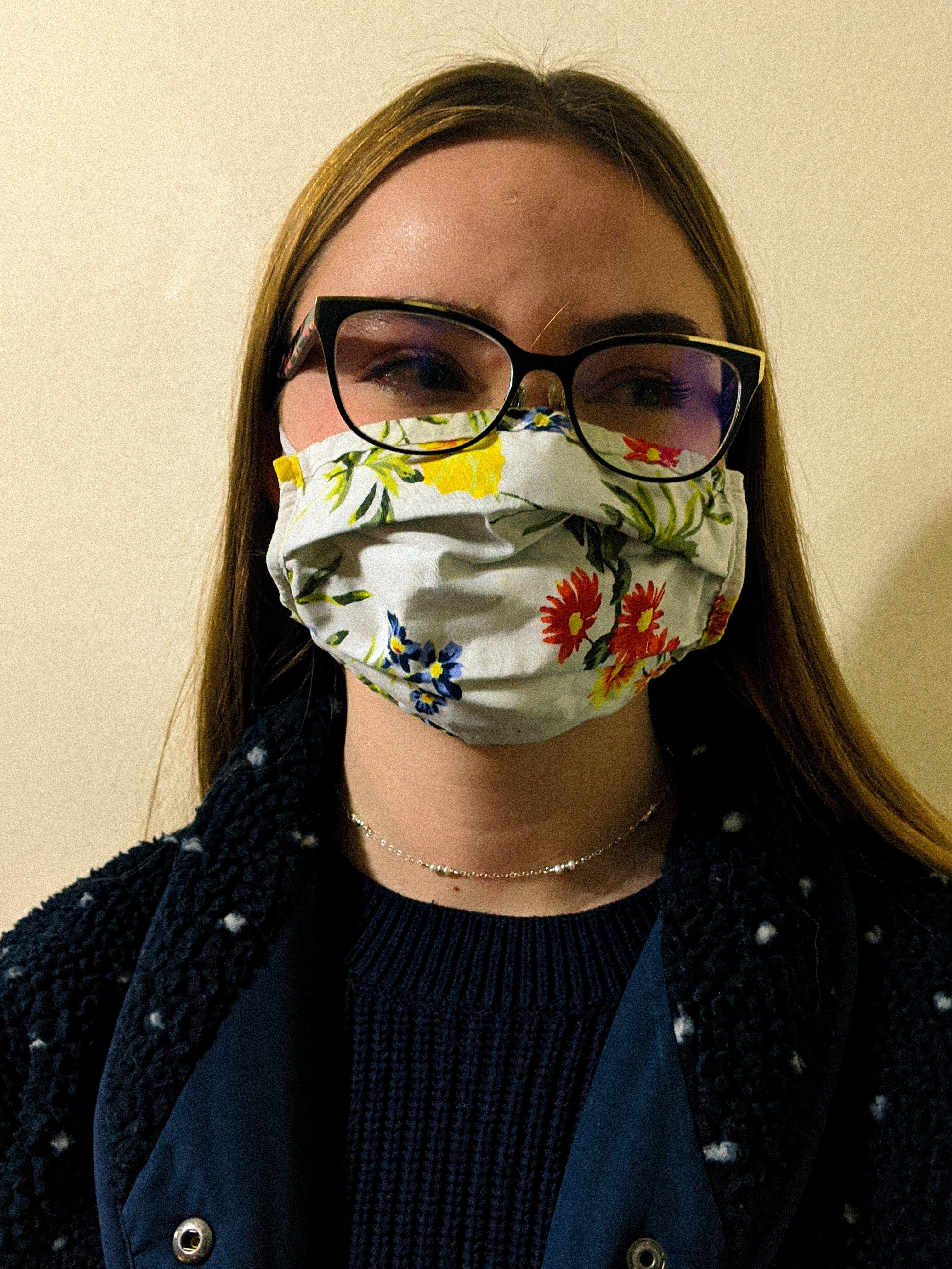 Close-up of white young woman with long hair and glasses, wearing a flowery face mask.