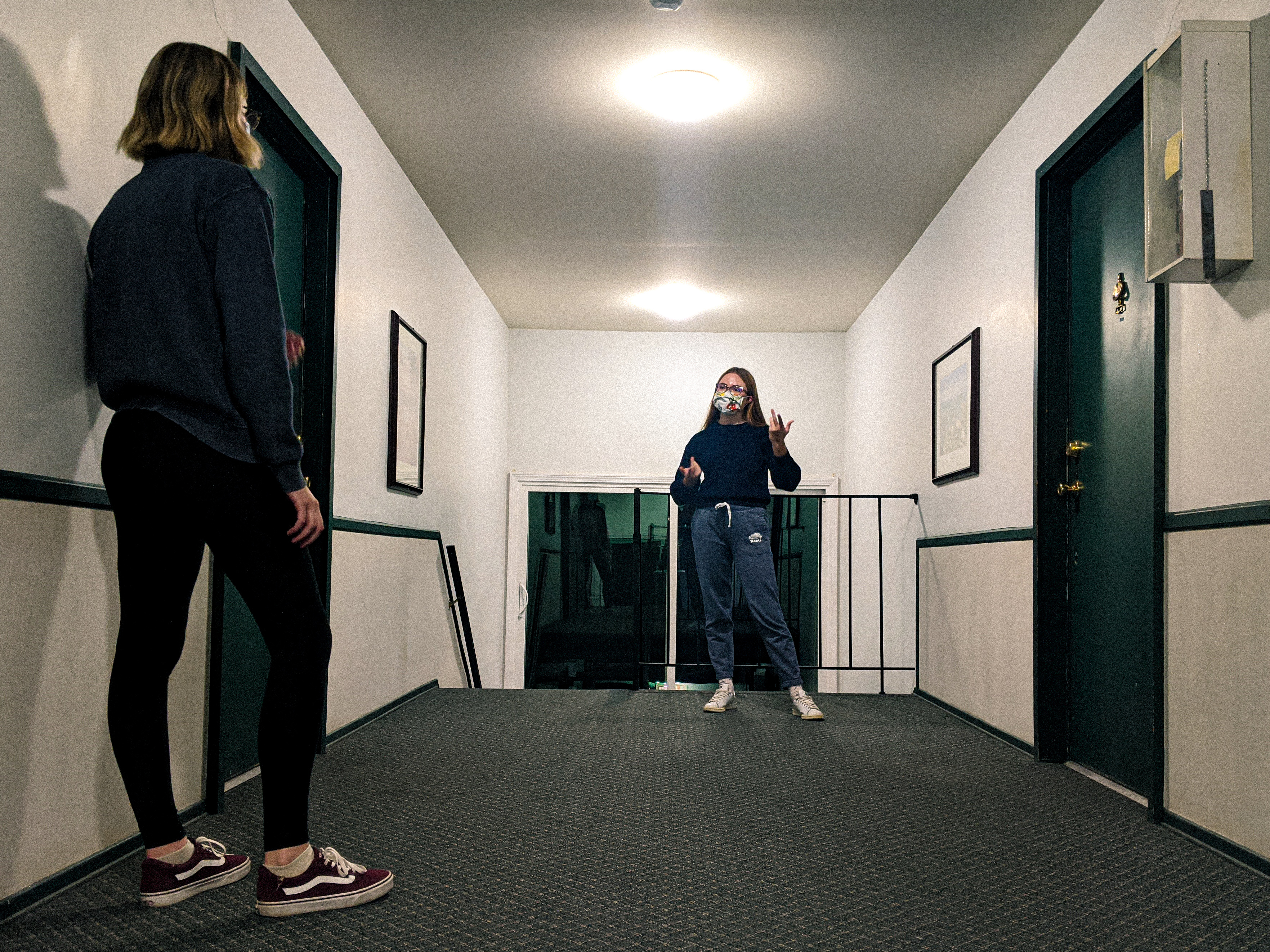 Two young women in a hallway, facing each other from at least six feet distance, wearing face masks.