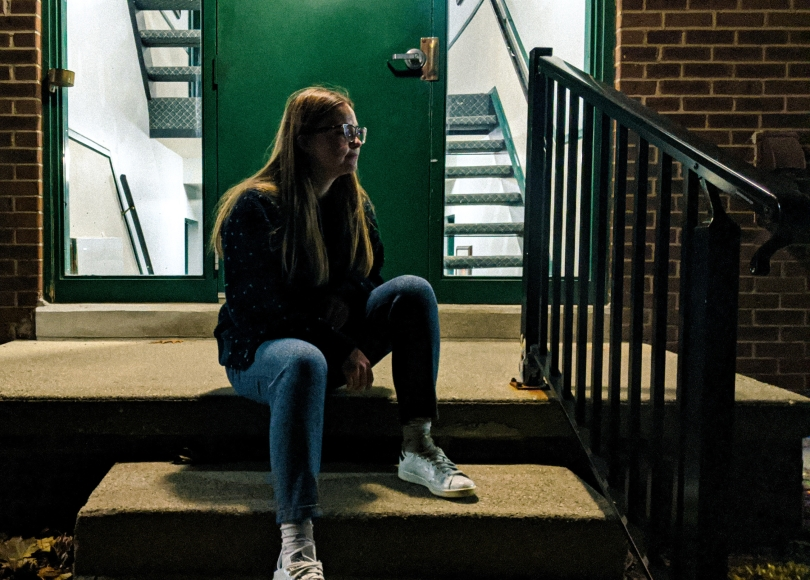 Young woman sitting on steps of apartment building in evening hours