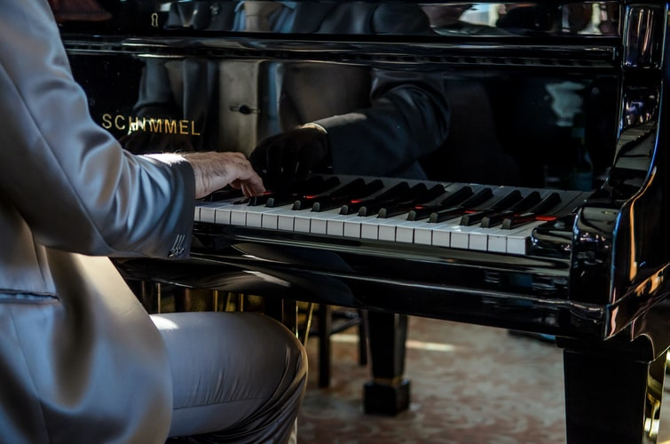 Man sits on bench playing piano, close-up on hands on keys