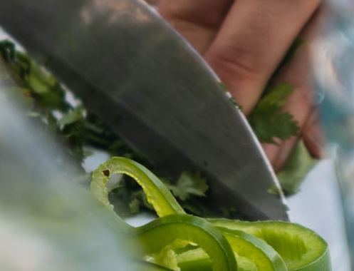 Hand chopping cilantro and green peppers with sharp knife