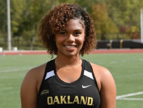 Close-up of smiling young black woman, wearing athletic top that reads Oakland, with athletic field visible behind her