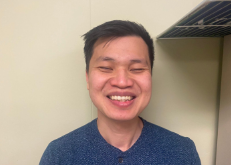 Close-up of smiling young man of Asian descent, short black hair, blue shirt