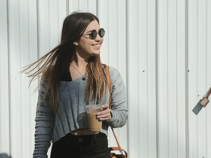 Young woman with coffee cup and sunglasses smiles outdoors, wind blowing her hair