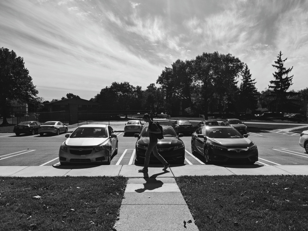 Black and white picture of young man walking with backpack in parking lot