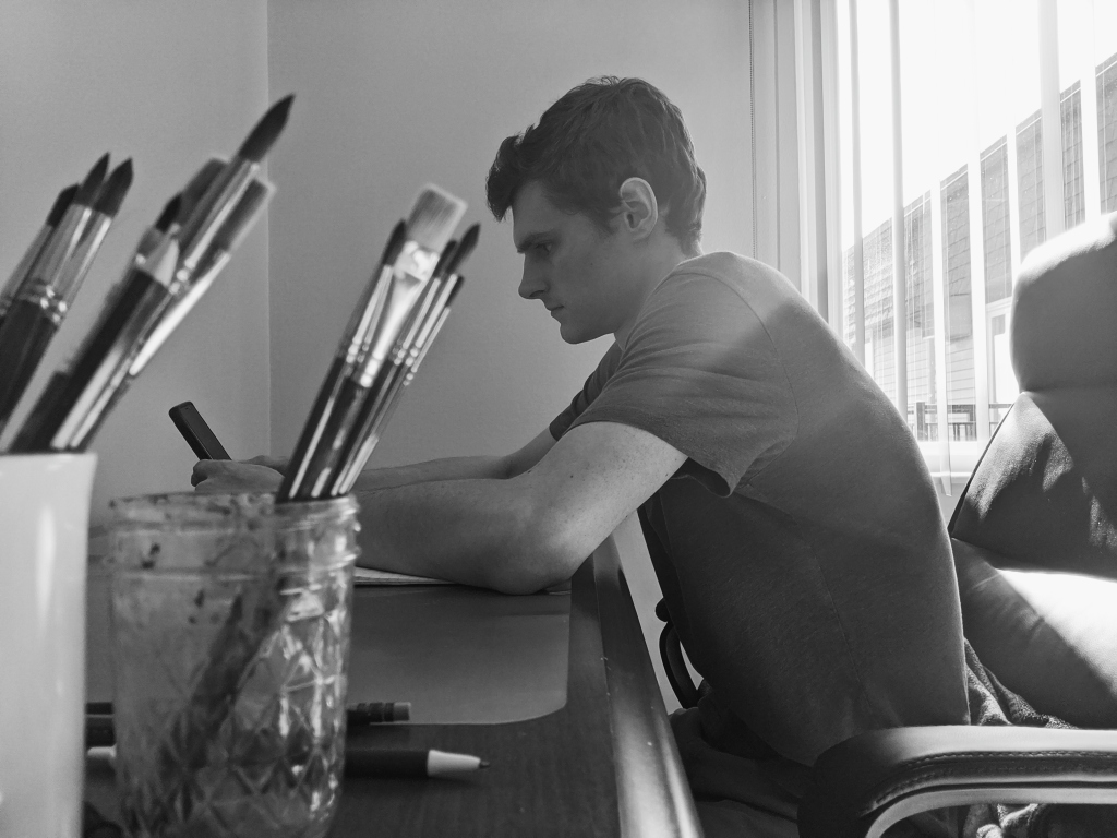 Black and white picture of young man sitting at desk, jars of paint brushes in the foreground