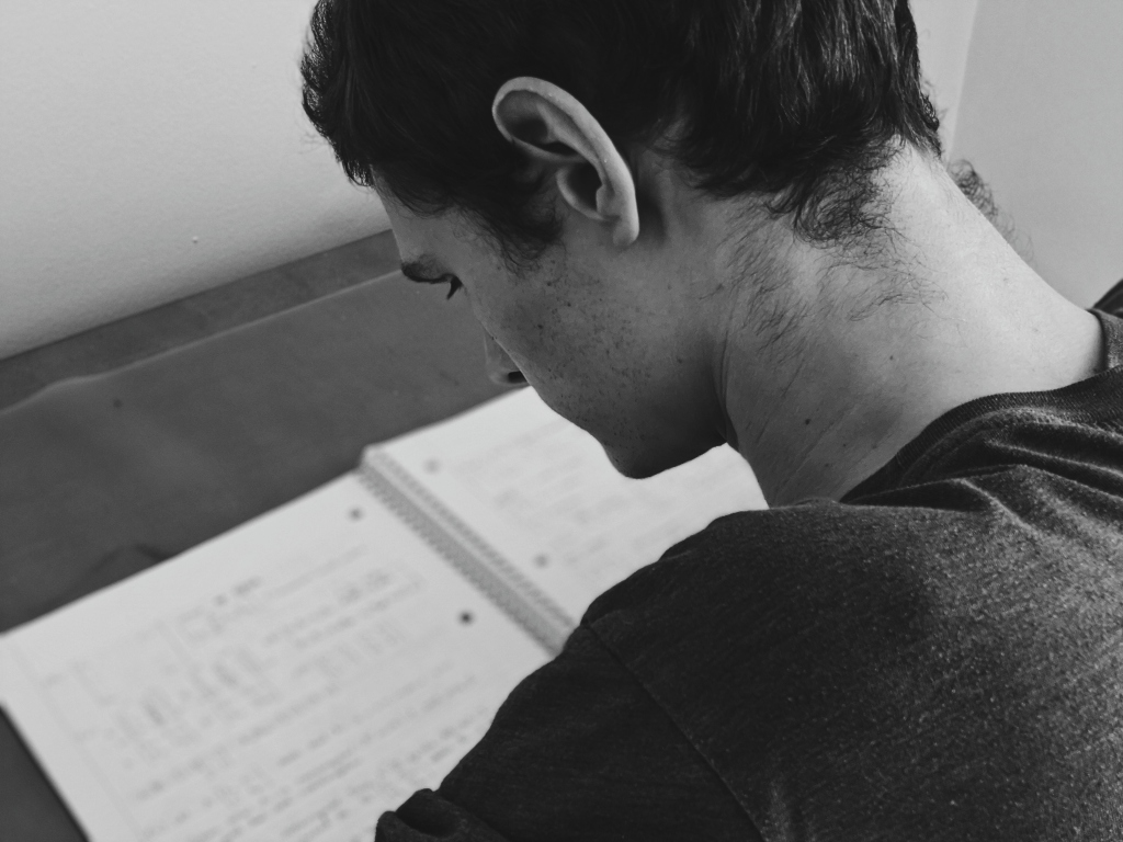 Black and white young man sits at desk reading notebook