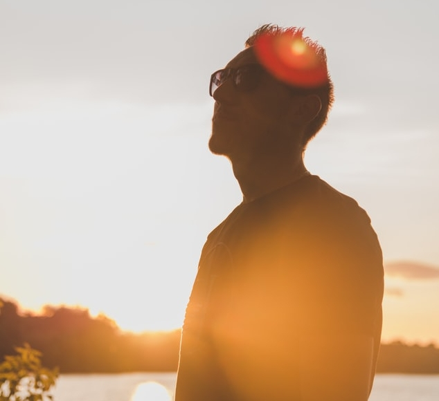 Silhouette of man with sunglasses, body of water and sun behind him