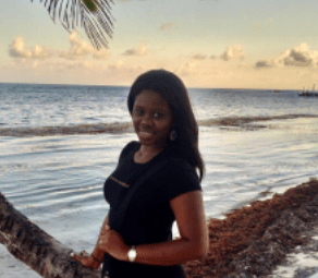 Young woman with dark skin, smiles by palm tree on beach, large body of water behind her