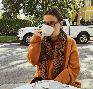 Young white woman with long hair in a ponytail drinks coffee at table outdoors, street view in the background