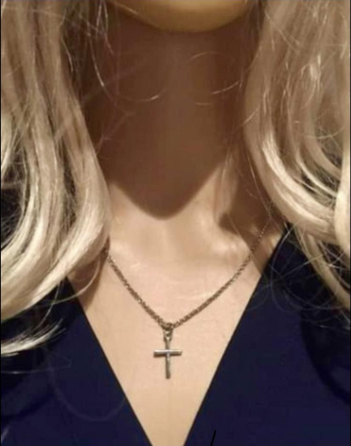 Close-up of white woman's neck, blond hair on her shoulders, gold cross on gold chain around her neck