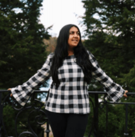 Young woman with long, black hair and white-and-black checkered shirt smiles on bridge with trees in the background
