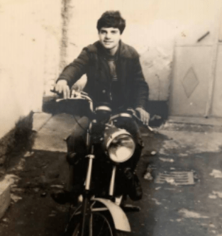 Black and white picture of young white man with black hair on motorcycle with large front light