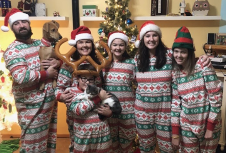Family of six, two adults, three daughters, and one son, smile in matching Christmas patterned pajamas by Christmas tree. Father holds small dog. Son in the front holds cat.